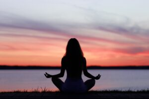 silhouette of a girl sitting in a lotus position on the background of sunset over the lake